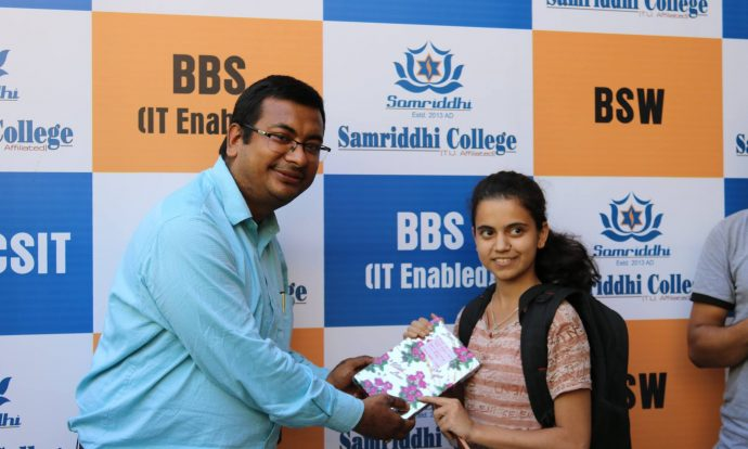 Topper of BSc.CSIT Mock Test Receiving gift from Principle Sir